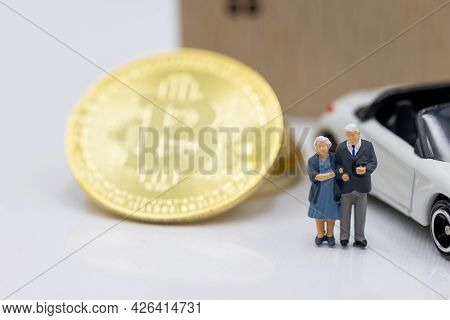 Miniature People Standing With Gold Bitcoin, House And Car.  Concept Of Business, Money, Technology,