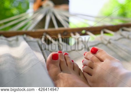 Woman Legs With Red Nail Polish On Hammock. Woman With Beautiful Pedicure Resting On Hammock At Sunn