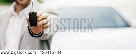 Photo Of Young Male Consultant Giving Car Key To Buyer After Successful Deal In Auto Show