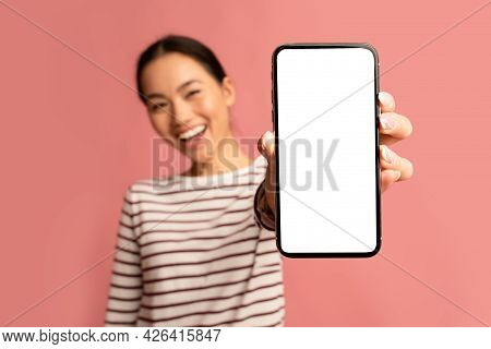 Great App. Cheerful Asian Female Demonstrating Smartphone With Blank White Screen