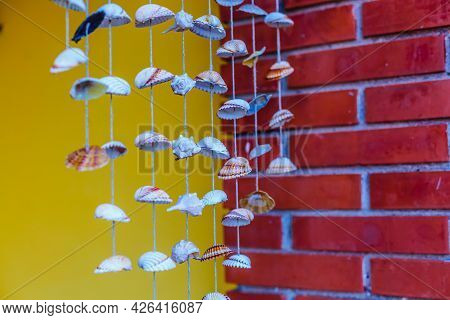 Sea Shell Hanging With Bokeh Background. The Hanging Curtains Made Of Shells Are Crafts Produced By
