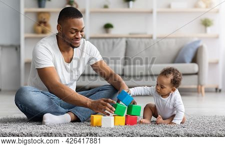 Happy Young Black Father Playing With His Infant Baby Son At Home