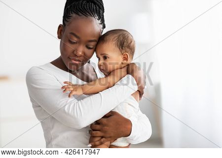 African American Nanny Hugging Her Cute Infant At Home