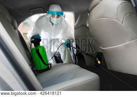 Worker In Hazmat Suit With Chemical Alcohol Spray Cleaning Inside Car To Disinfect