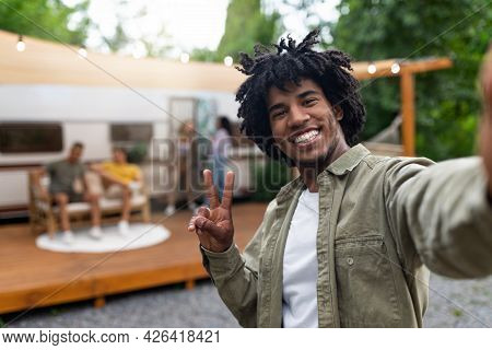 Black Guy Taking Selfie Near Motorhome, Gesturing Peace, Resting With His Multiracial Friends Outdoo