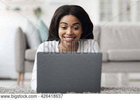 Remote Job Opportunities. Cheerful African American Woman Working On Laptop At Home, Lying On Floor