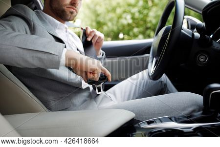 Be Safe Young Guy Sitting In Driving Seat Of Car, Fastening Safety Belt And Ready To Go