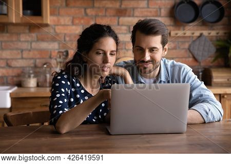Happy Millennial Couple Using Laptop In Kitchen, Watching Show Together