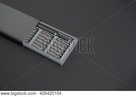 A Set Of Screwdrivers With Bits In A Case On A Dark Background. Close Up, For Work, Copy Space, Spac
