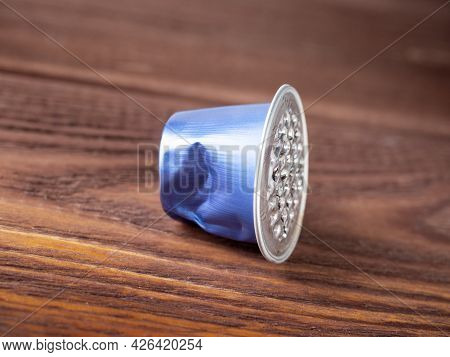 The Used Blue Aluminum Capsule For The Coffee Machine Lies On A Brown Wooden Background. The Concept