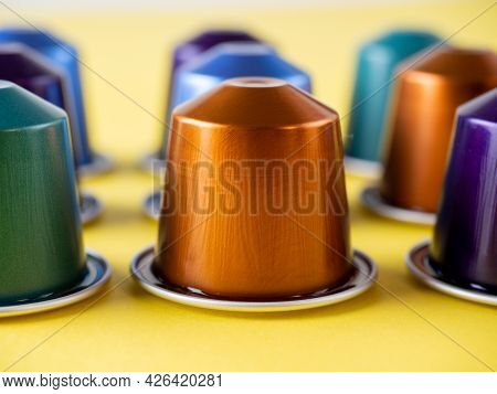 Many Aluminum Coffee Capsules Are Displayed In A Row On A Yellow Background. Food Pattern. Capsules