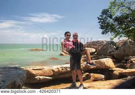 A Caucasian Man Holding A Chinese Woman On The Rocks Within The Penang National Park In Malaysia On