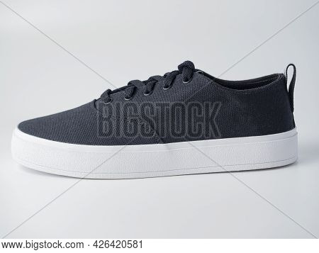 Close-up Of Black Canvas Sneakers Isolated On A White Background. Prokukt Shot, Side View