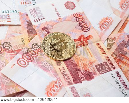 The Bitcoin Coin Lies On The Background Of Russian Rubles. Cryptocurrency Mining And Mining Concept