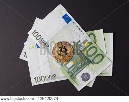Gold Bitcoin Is In 100 Euro Bills. The Concept Of Cryptocurrency And Money. Top View, Black Backgrou