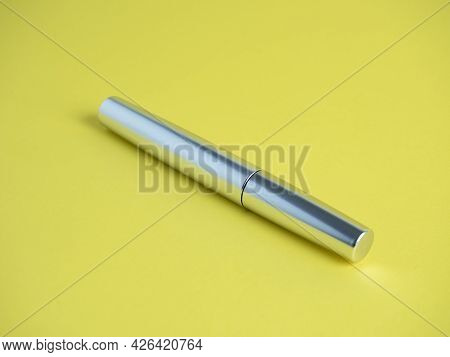 Close-up Of A Closed Mascara Of Silver Color On A Bright Yellow Background.