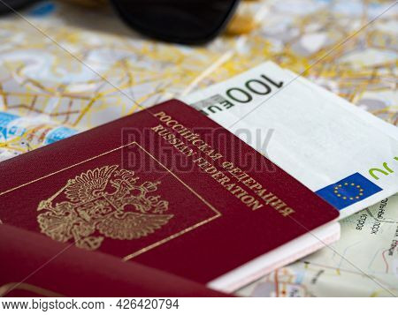 A Close-up Of A Russian Passport With Embedded Euro Bills Is On The Map. The Concept Of Travel And R