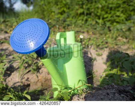 Close-up Of A Plastic Green Watering Can With A Blue Spout Standing On The Ground In The Garden. The
