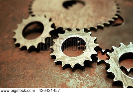 Metal Gears Of Different Sizes On A Metal Surface. Rough Ironwork