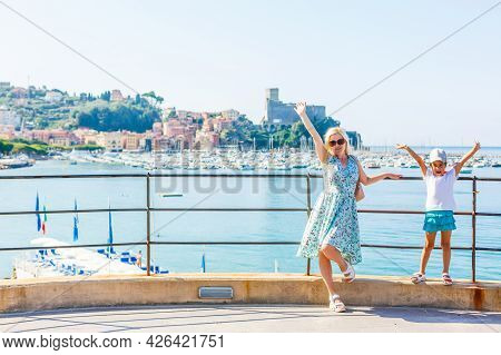 Mother And Daughter At Lake Garda With Mountains, Lake And Town On The Background. Lake Garda Is The