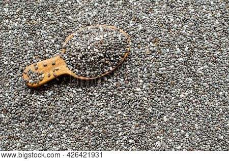 Closed Up Dry Organic Chia Seed Pile In Wooden Spoon On Chia Seed Background. Concept Of Natural And