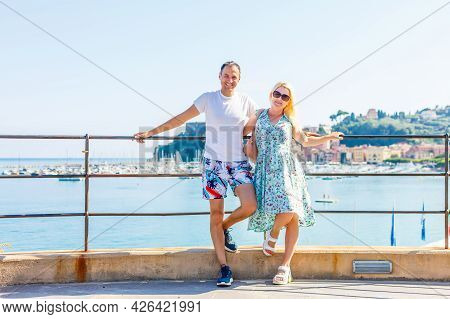 Travel Italy, Europe. Smiling Couple In Love At Lake Garda With Mountains, Lake And Town On The Back