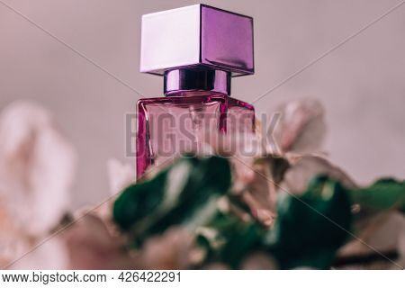 Lilac Glass Bottle Of Eau De Toilette Or Perfume With Square Cap On Light Plaster Surface With Apple