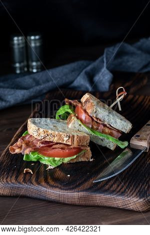 Two Halves Of A Bacon And Tomato Sandwich On A Wooden Board Against A Dark Background.