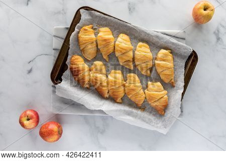 Top Down View Of Baked Apple Filled Crescent Rolls On A Parchment Lined Baking Sheet.