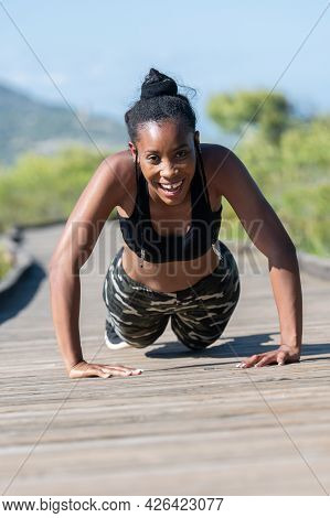 Struggling Afro American Woman Doing Push Ups On A Wooden Runway: Exercise And Effort Concept.