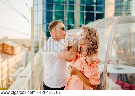 Man And Woman Drink Champagne On Bruderschaft In A Rooftop Cafe.