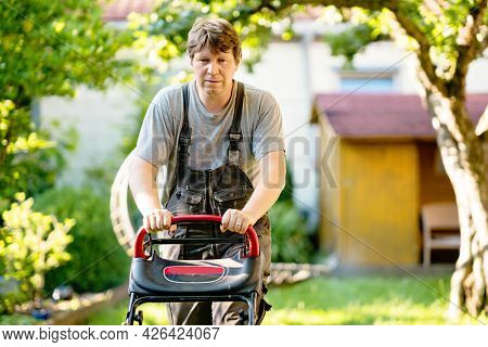 Happy Young Man With Lawn Mower. Portrait Of Smiling Man Working In Garden, Trimming Grass. Garden W
