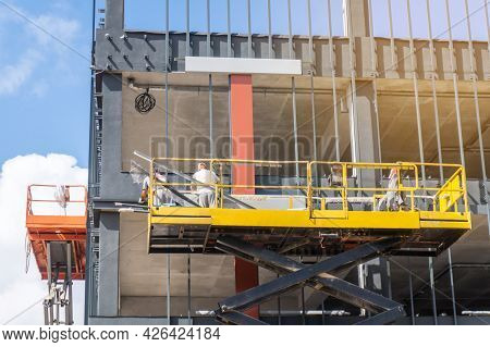 Workers On A Scissor Lift Platform At A Construction Site