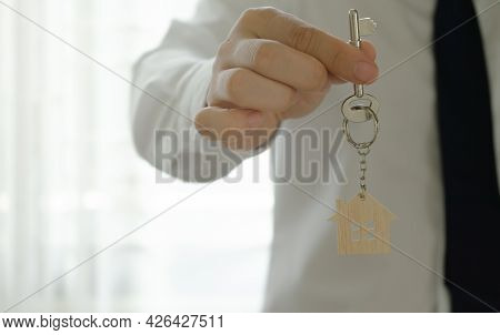 Bank Officer Or House Seller Agents Giving House Key After A Successful House Purchase Agreement.