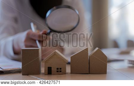 Woman Bank Officer Or Appraiser Using Magnifying Glass To Check Miniatures House Model. The Concept