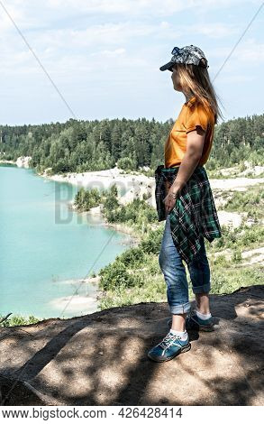 Rear View Of A Young Blond Woman Traveler In A Cap And Ginger T-shirt Standing On The Cliff Of Blue