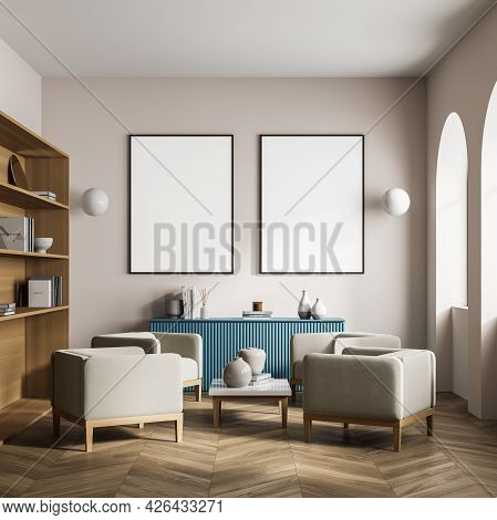Beige Colour In The Waiting Room Interior With Two Posters On The Wall, Four Armchairs With Coffee T