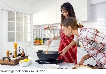 Cute Joyful Couple Cooking Together And Adding Spice To Meal, Laughing And Spending Time Together In
