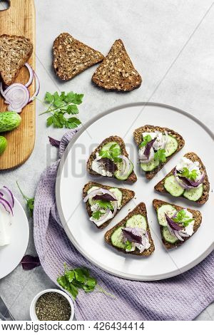 Canapes With Toasted Bread With Sunflower And Flax Seeds, Feta Cheese, Cucumber And Onion. Flat Lay,