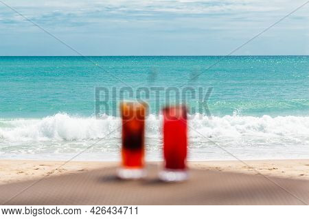 Blurred Defocused Fresh Exotic Cocktails On Table, Holidays In Paradise Concept. Iced Raspberry And