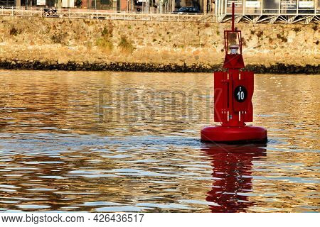 Red Signaling Beacon Floating In The Douro River In Porto. Promenade In The Background