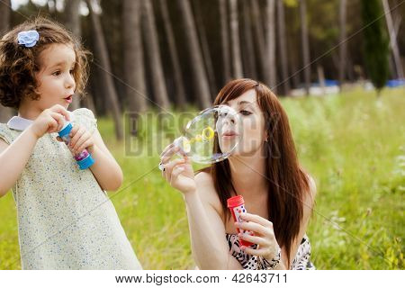 Young mother and her child playing with soap bubbles