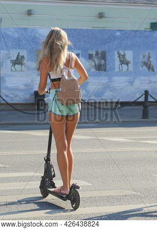 A Blonde Girl In Short Shorts Rides A Scooter On A Pedestrian Crossing, Nevsky Prospekt, St. Petersb