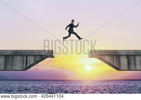 Businessperson Jumping Over Concrete Gap On Beautiful Sunset Background. Success And Challenge Conce