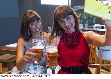 Two Female Friends Take A Selfie While Drinking Beer In A Pub