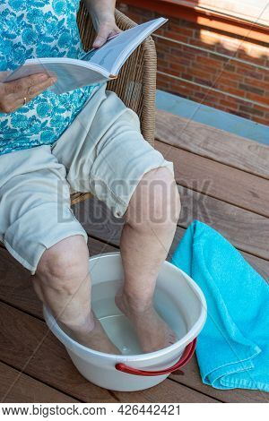 Senior Woman Relaxing Reading Book And Soaking Feet In The Cold Water. How To Stay Cool In Hot Weath