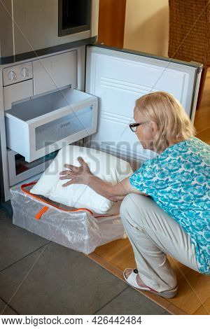 Senior Woman Putting Pillow In The Fridge Freezer. How To Stay Cool In Hot Weather. Beat The Heat.