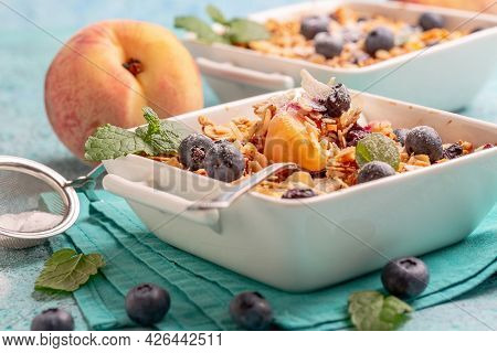 Peach Crumbs With Blueberries, Oatmeal And Almond Flakes In A Saucepan On A Linen Napkin. Concept Of