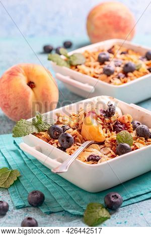 Peach Blueberry Crumbs, Oat Flakes And Almond Flakes Are Served With Vanilla Ice Cream. Concept Of H