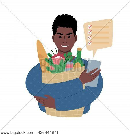 Young African Man With Groceries Bag And A Shopping List On A Smartphone.